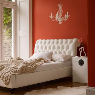 Bedroom with orange walls and white furniture