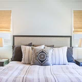 white bedroom with black headboard and white bed sheets