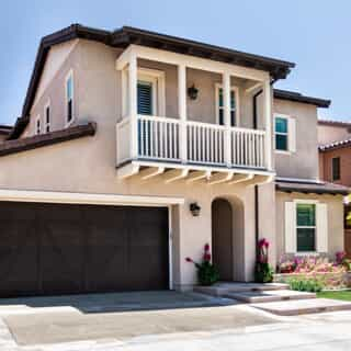 Tan exterior home with brown trim and brown garage door