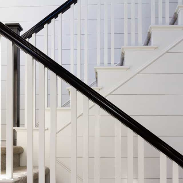 white wood stairwell with black handrails