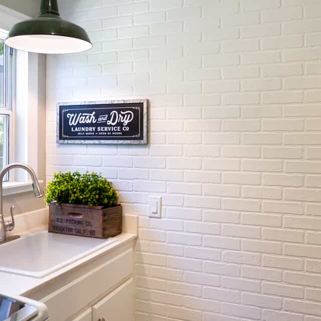 white kitchen with plant next to sink and light turned on