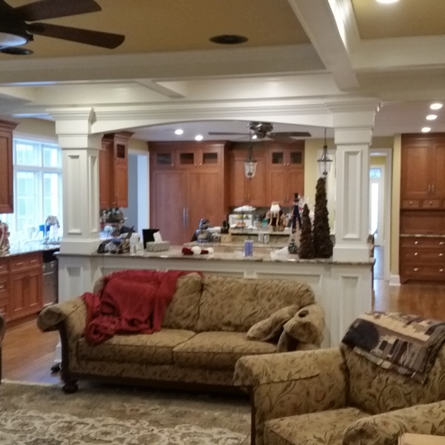 tan living room with brown couches and wood cabinets