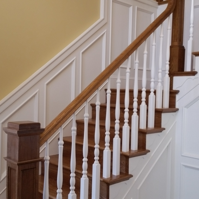 yellow and white stairwell with wood handrails