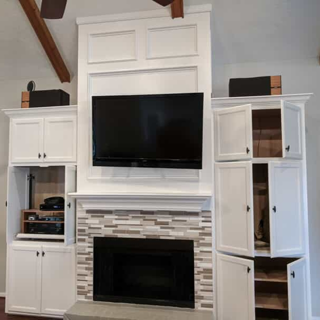 White fireplace and cabinets with tv mounted to wall