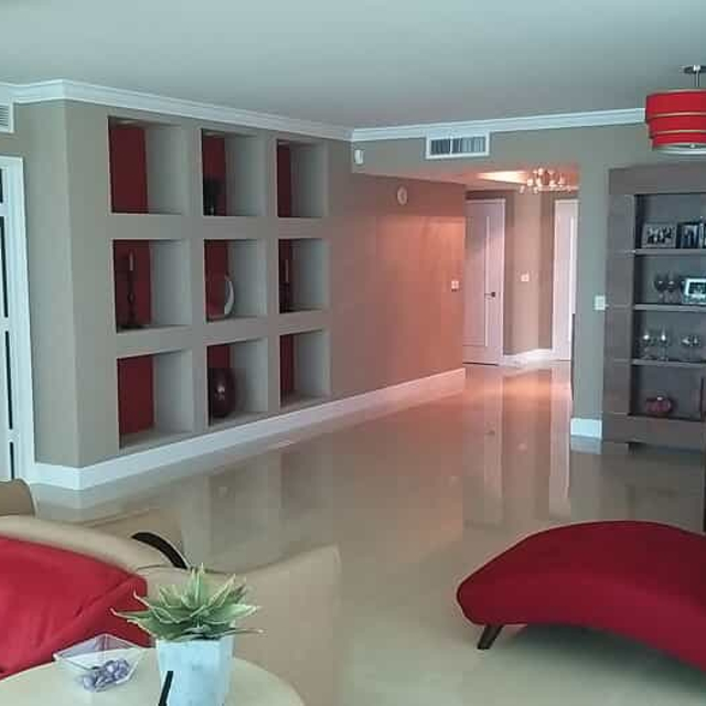 Living room with red furniture and beige walls