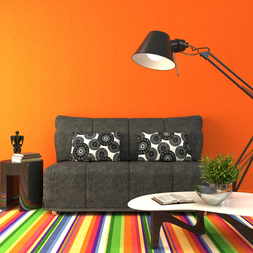 Bright dorm room with orange walls, rainbow rug and charcoal colored furniture