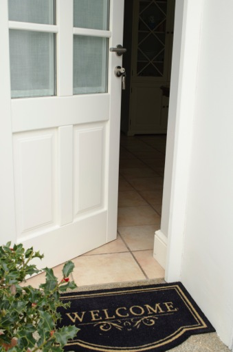 Open front door with welcome mat