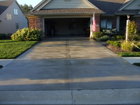 Clean and wet driveway in front of an open, empty garage