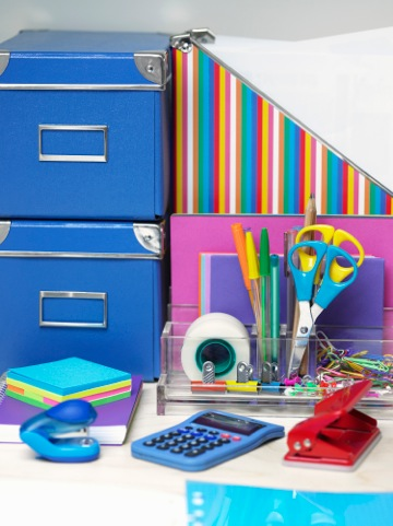 Brightly colored office supplies including folders, scissors, sticky notes, small stapler, pens, tap, three whole punch and more