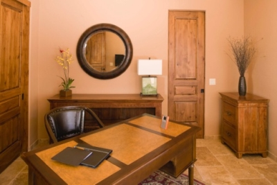 Beige walled office with medium colored wood furniture, dark wood accents and personal touches including a painting, flower arrangements and mirror