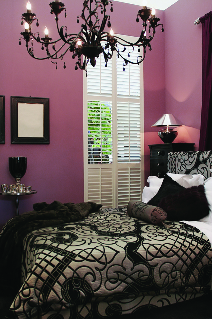 Bedroom with chocolate accents, chandelier and raspberry colored walls