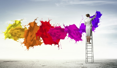 Image of Woman on Ladder Painting a Neutral Sky with Splashes of Bright Colors