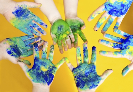 Childrens' Hands Covered in Green, Blue and Yellow Paint After Finger Painting