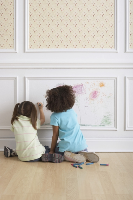 Children coloring on white wall panel