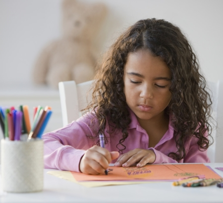 Child Coloring Picture with Crayon on Colored Paper