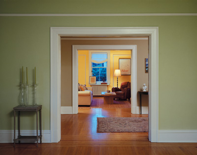 Green Painted Walls with White Trim and View into Other Beige and Yellow Rooms of the Home