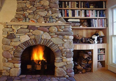 Stone fireplace next to a bookshelf