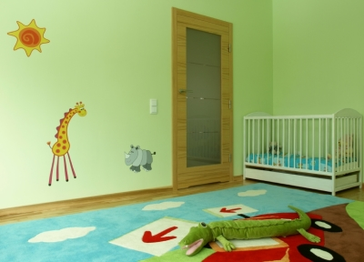 Bright green painted nursery with cartoon animal decals
