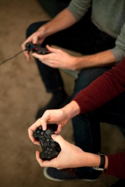 Closeup of two sets of hands holding video game controllers