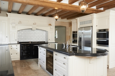 Beautiful kitchen with crisp white cabinets, black stone counters, island, and exposed beams.