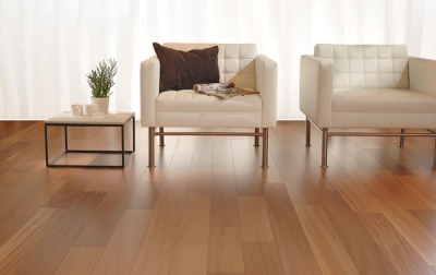Two white chairs in a living room with light-colored wooden floors