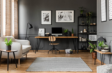 Interior of a living room with wood flooring, grey painted walls, a couch, desk and shelves.