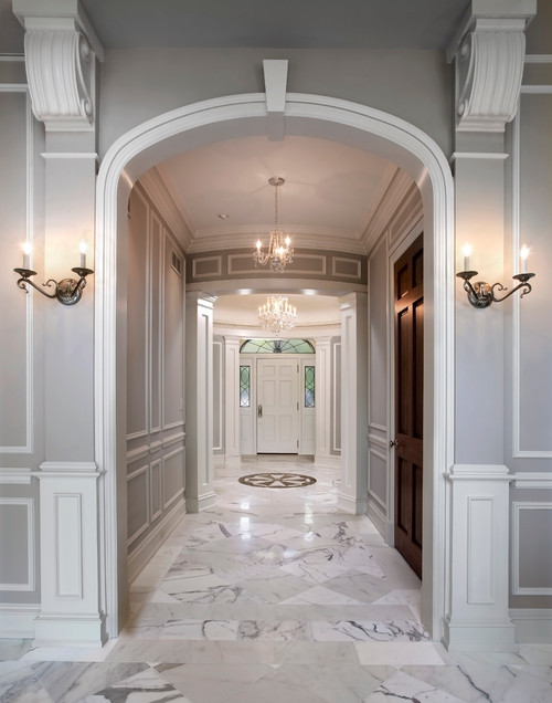 Hallway with marble floors leading to a front door