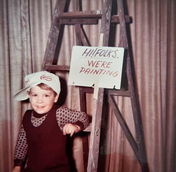 "Dave Young Child Photo next to white sign that says ""hi folks we're painting"""